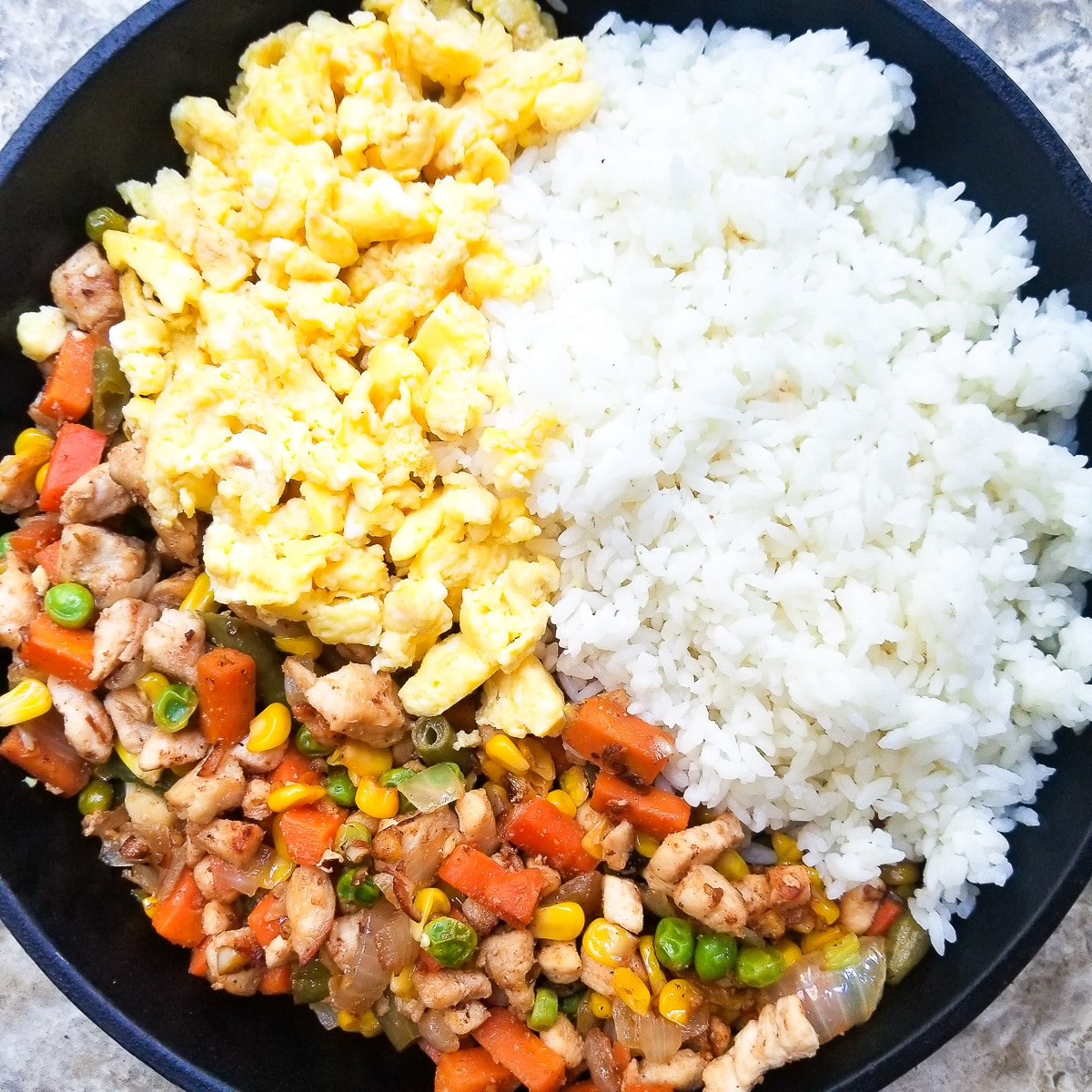 Veggie mix, scrambled eggs and white rice in cast iron skillet.
