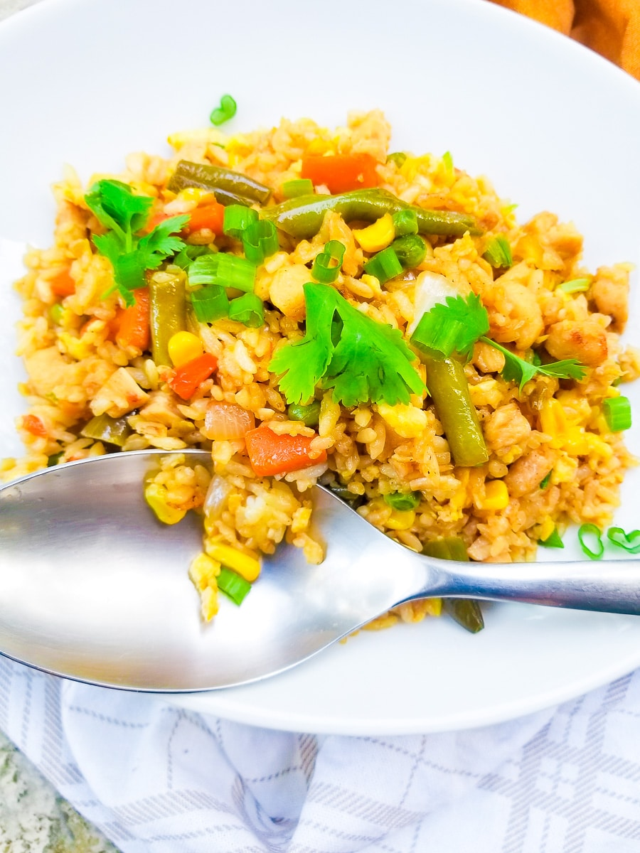 Arroz Chino (Chinese Fried Rice) served in a white oval platter, topped with cilantro sprigs. A large white spoon for serving.