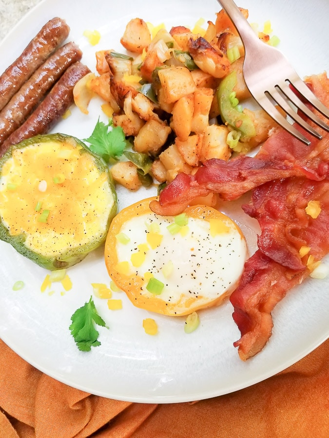 Bell Pepper Eggs with home fries, sausage and bacon served on a white plate.