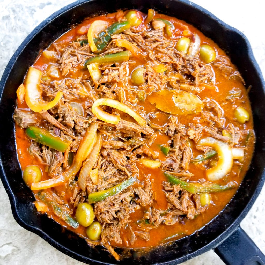 Carne deshebrada fully cooked in a cast iron skillet and ready to eat.