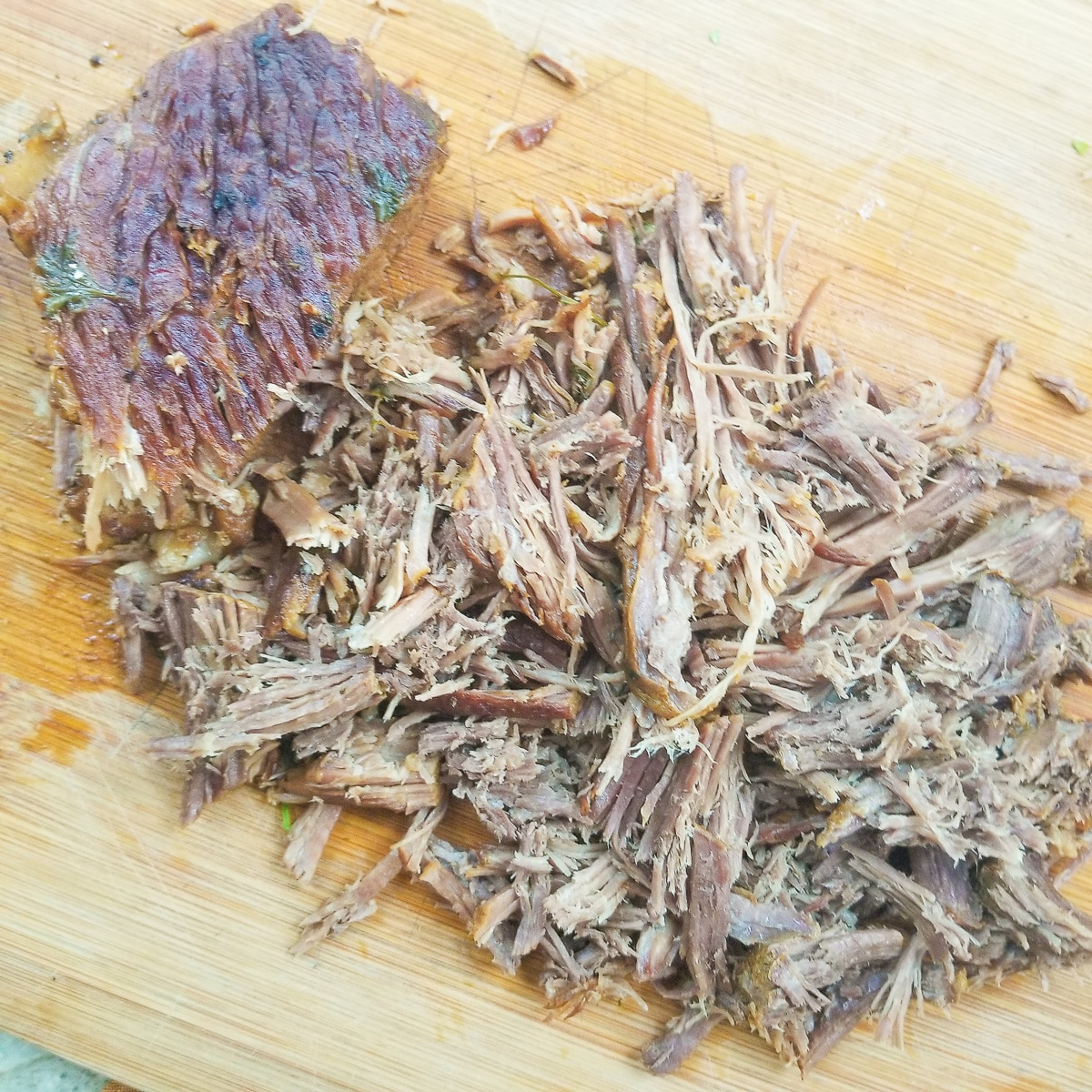 Beef on a wooden cutting board, shredded to make carne deshebrada.