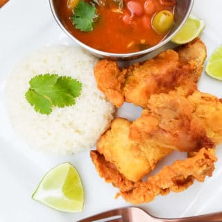 Chicharrones de Pollo served alongside white rice, Puerto Rican stewed beans and lime wedges.