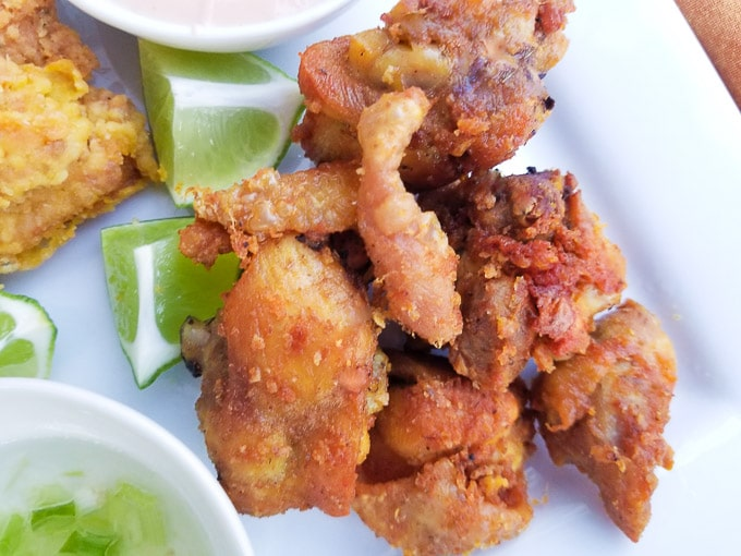 Chicharrones cooked without flour coating served alongside sauces on a white platter.