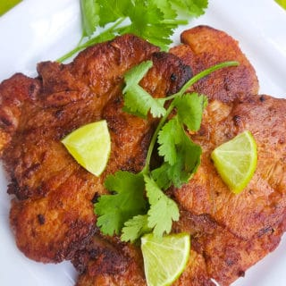 Puerto Rican Fried Pork Chops served on a white platter and topped with lime wedges.
