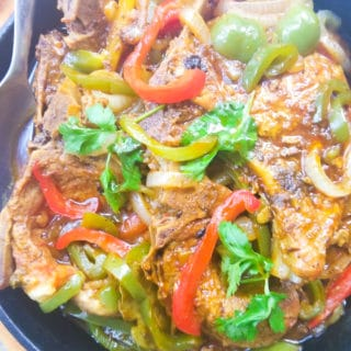 Chuletas Guisadas (Puerto Rican Stewed Pork Chops) cooked in a cast iron skillet, covered with onions, peppers and cilantro sprigs.