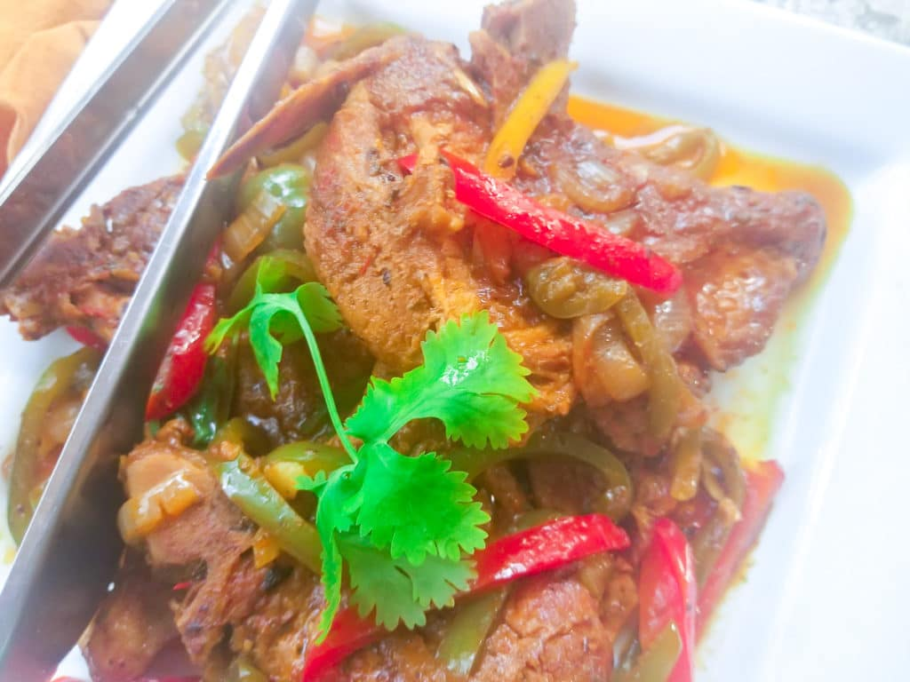 Chuletas Guisadas served on a white platter and topped with peppers, onions and cilantro sprigs.