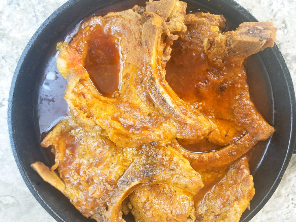 Chuletas guisadas cooked in a cast iron skillet.