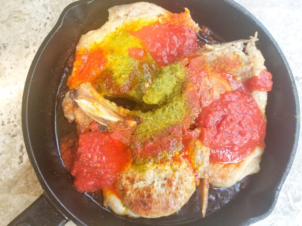 Pork Chops in a cast iron skillet topped with sofrito, tomato sauce, sazon, chicken bouillon, bay leaf and vinegar.