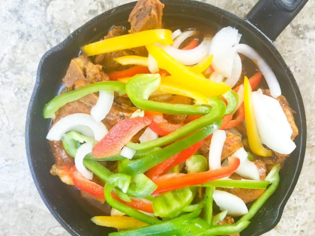 Chuletas guisadas cooked in a cast iron skillet, topped with raw onions and peppers.