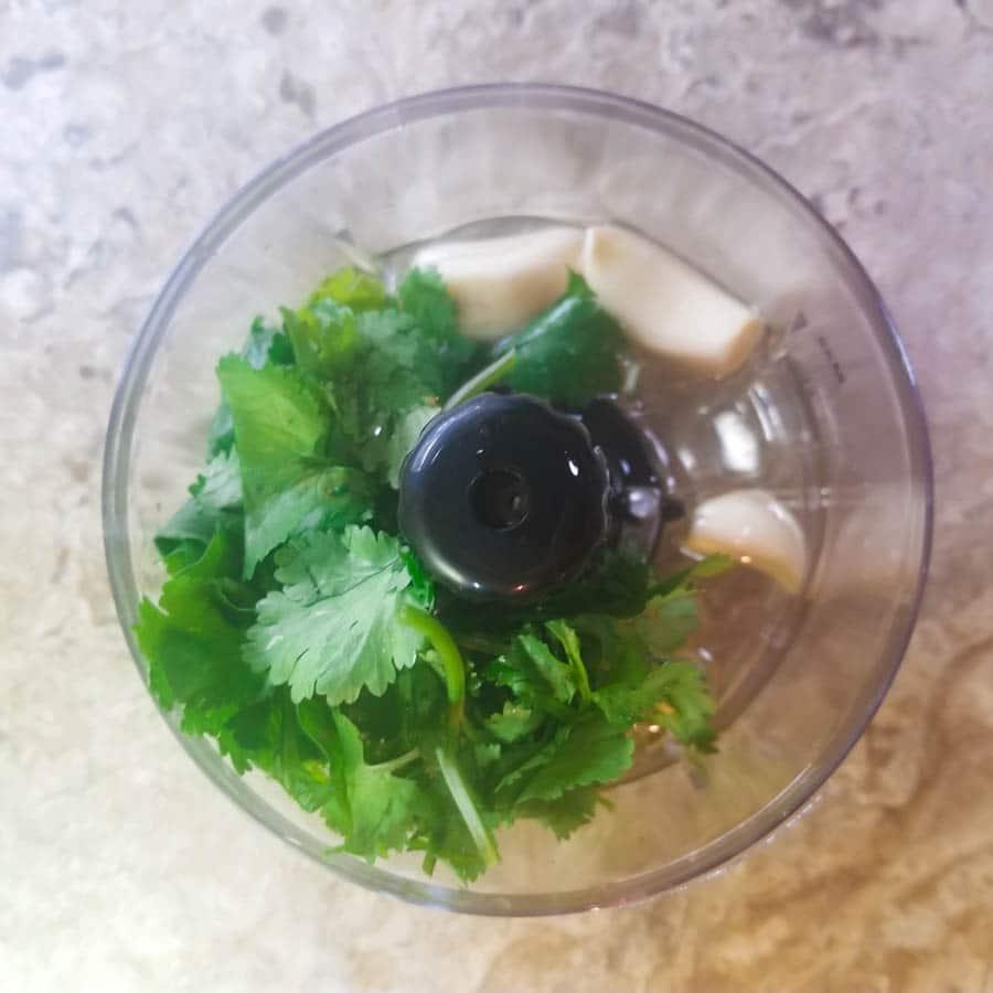 Cilantro, garlic and oil in a small food chopper for cilantro garlic salsa.