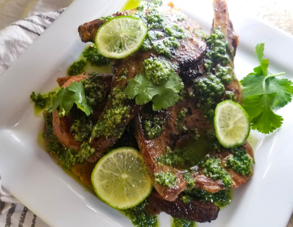 Chuletas con Salsa de Cilantro (Pork Chops with Cilantro Sauce) served on a white platter and topped with slices of lime.