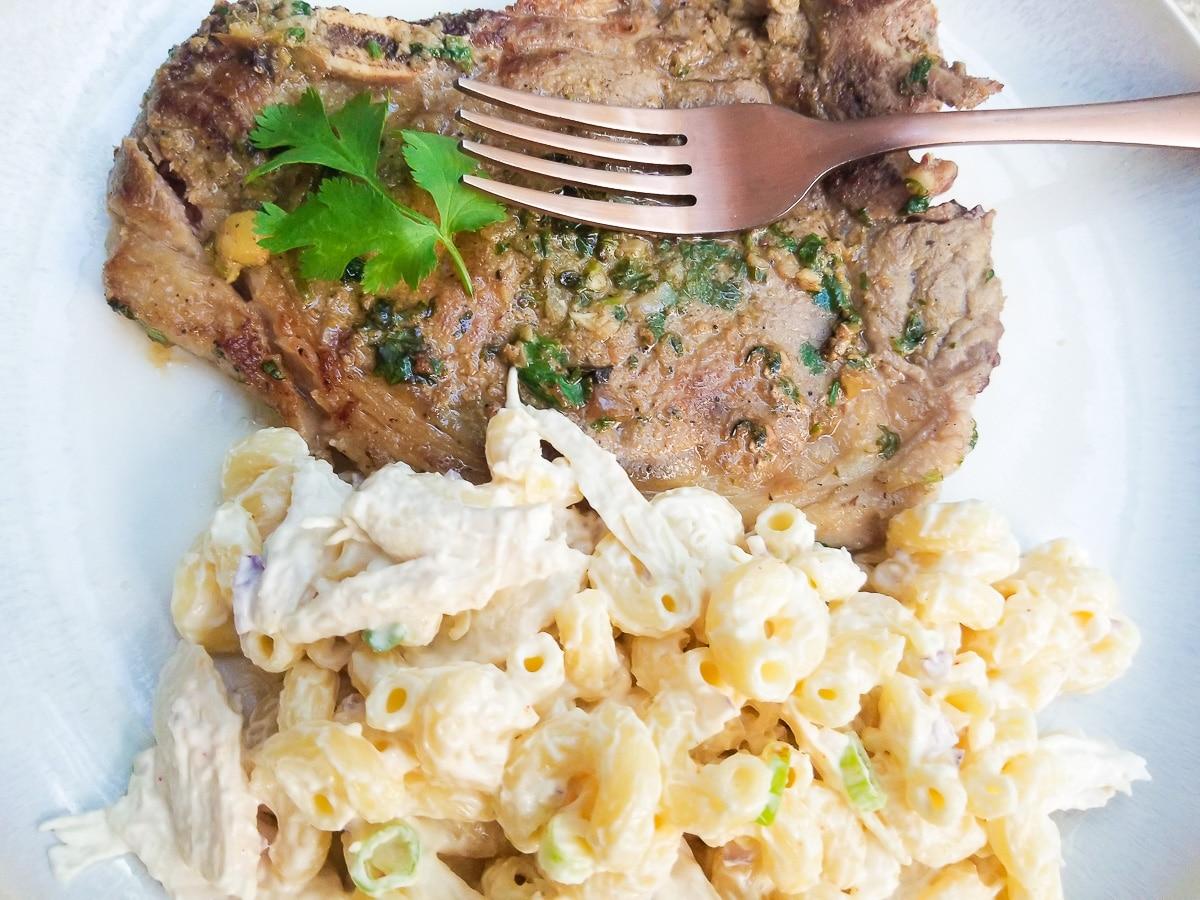 Chuleton a la plancha (Ribeye Steak) served on a white platter with a side of macaroni salad (coditos).