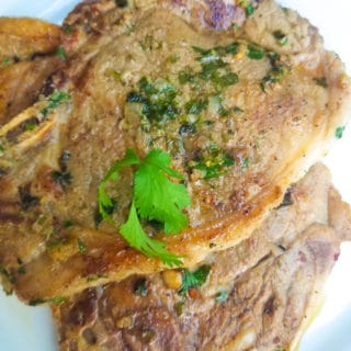 Chuleton a la plancha (Ribeye Steak) served on a white platter and topped with cilantro sprigs for garnish.