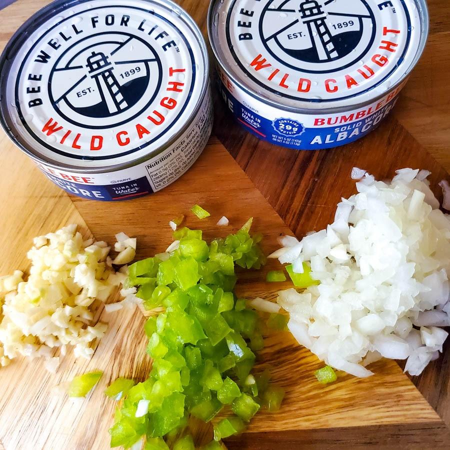 Ingredients to make tortitas de atun (tuna cakes) on a wooden cutting board.