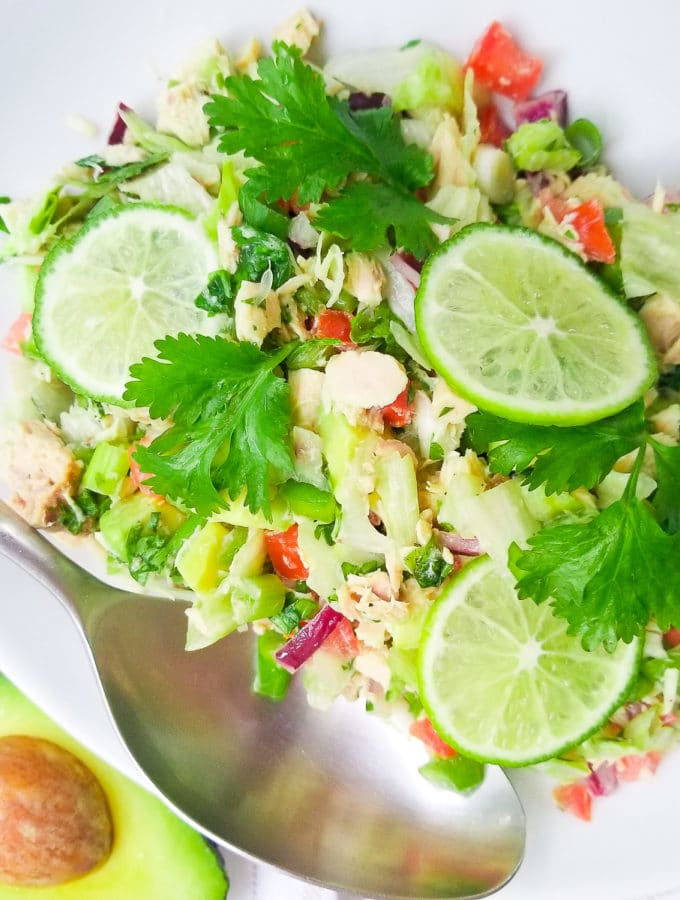 Ensalada de Atun in a white bowl topped with cilantro sprigs and slices of lime.