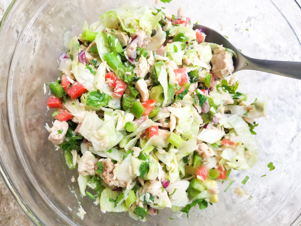 Tuna and all other ingredients combined in a glass bowl.