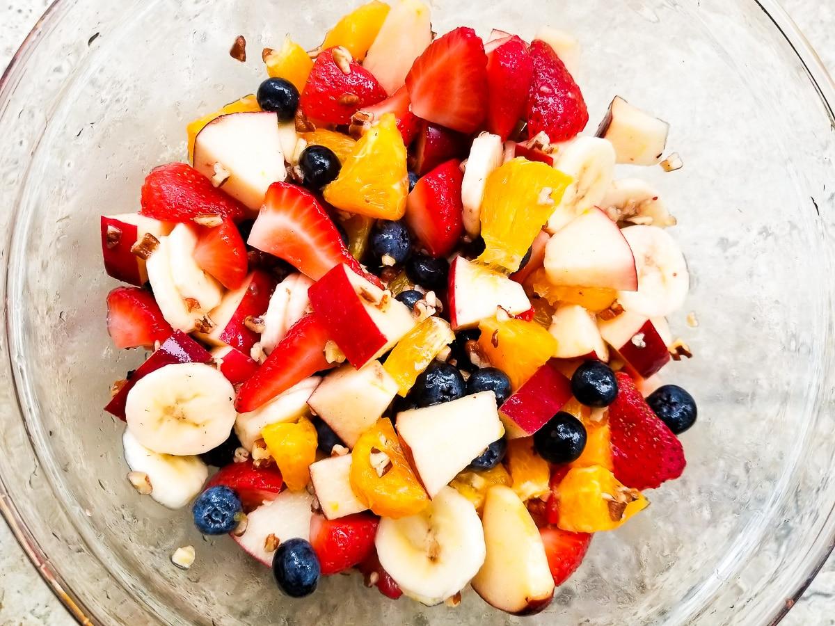 Ensalada de frutas (fruit salad) mixed together in a glass bowl.