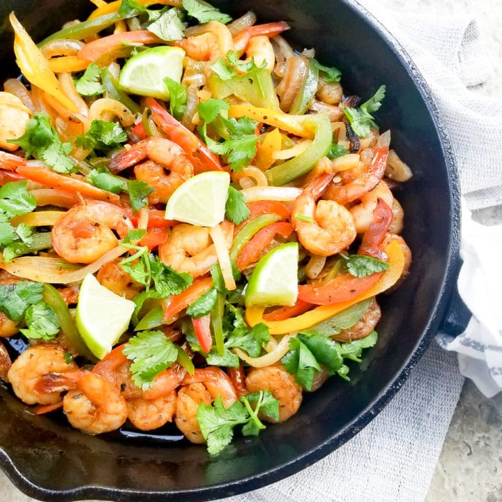 Cooked Shrimp Fajitas in a cast iron skillet, topped with chopped cilantro and lime wedges.