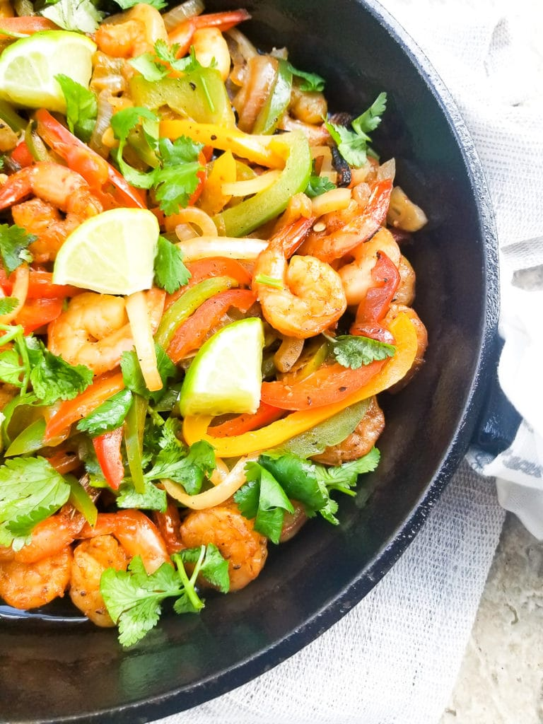 Cooked Fajitas de Camarones (Shrimp Fajitas) in a cast iron skillet, topped with chopped cilantro and lime wedges.