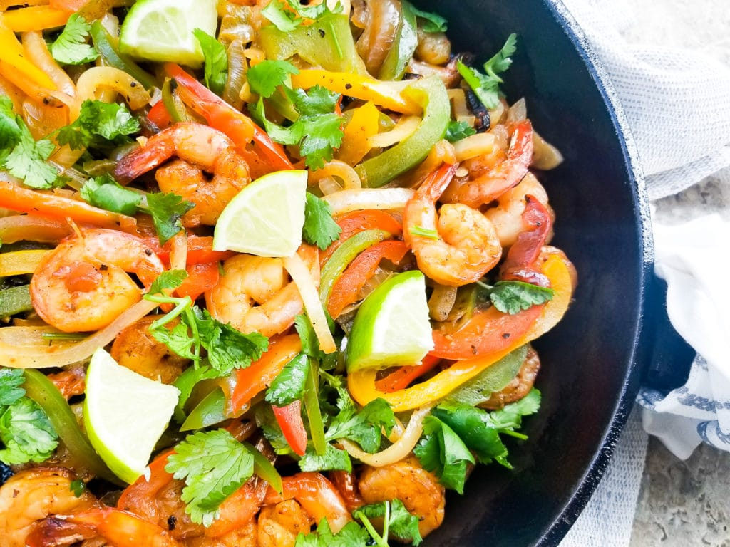 Cooked Shrimp Fajitas-Fajitas de Camarones in a cast iron skillet, topped with chopped cilantro and lime wedges.