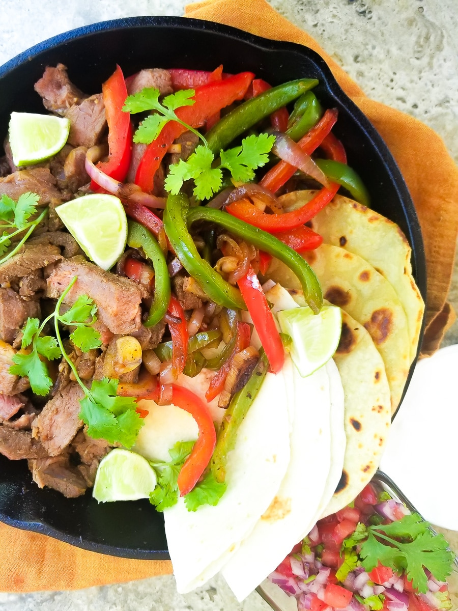 Fajitas de Res (Beef Fajitas) served in a cast iron skillet with green, red peppers, onions, burrito and corn wraps, topped with cilantro sprigs and lime wedges.