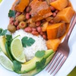 Habichuelas Guisadas con Calabaza served with white rice, avocado slices and lime wedges.