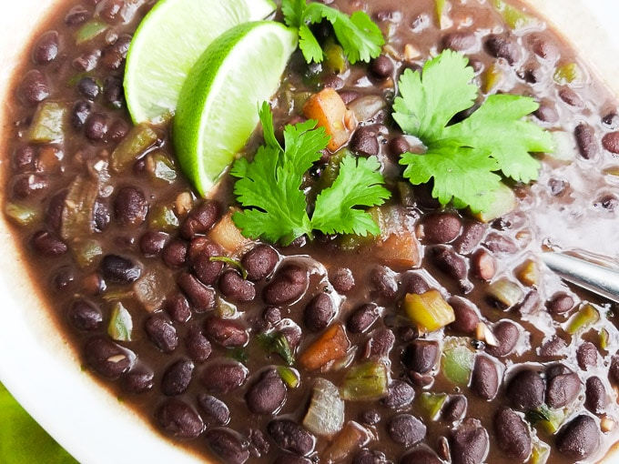 Black Beans Latin style in a white bowl and topped with lime wedges.