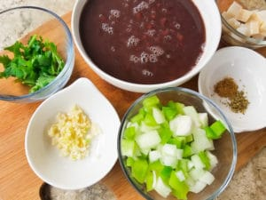 All the ingredients to make black beans in small bowls on top of a wooden cutting board.