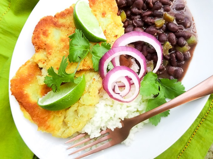 Black Beans Latin style served with white rice and bistec empanizado in a white bowl topped with lime wedges.