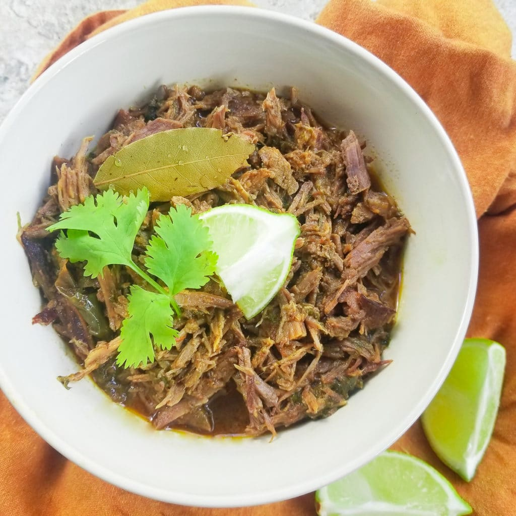 Instant Pot Shredded beef fully cooked and served in a light clay bowl, topped with fresh cilantro and lime wedges.