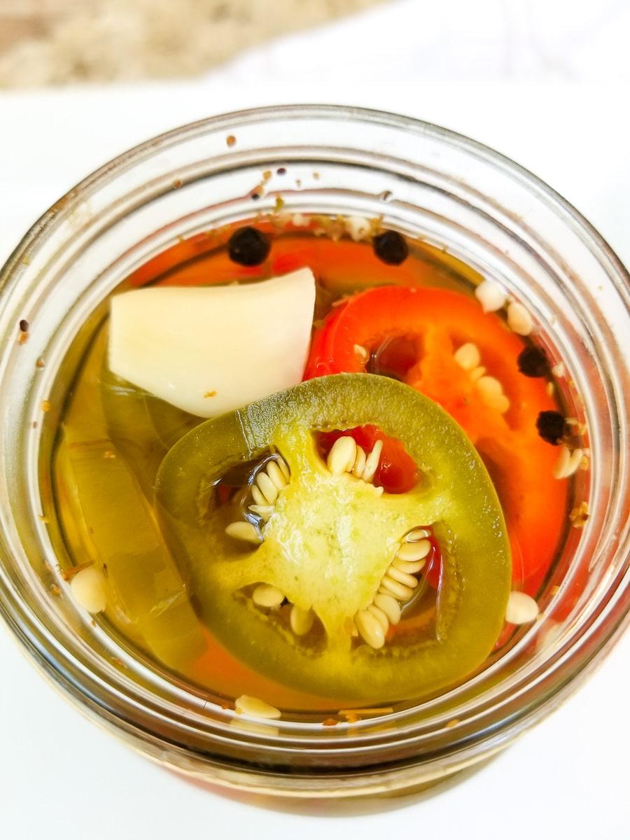 Top view of mason jar filled with jalapenos en vinagre (pickled jalapenos).