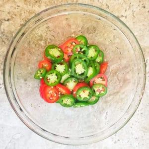 Sliced jalapenos in a transparent bowl.
