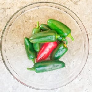 Whole jalapenos in a transparent bowl that have been rinsed.