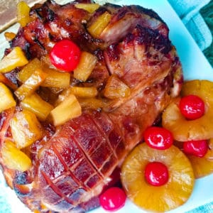 Jamon al Horno con Pina (Baked Ham with Pineapple Glaze) fully cooked in a baking tray and topped with pineapple glaze and pineapple chunks.