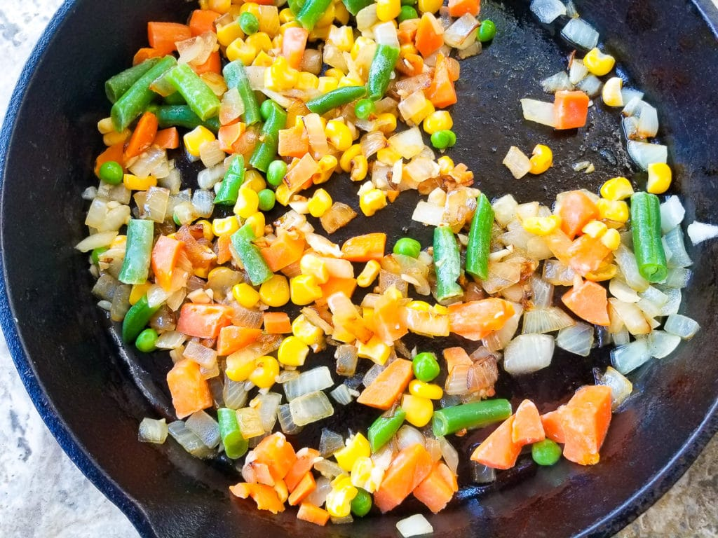 Veggies added to skillet of garlic, butter and onions.