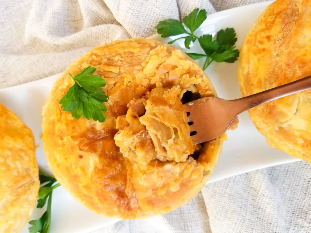 Mini turkey pie with the top cut open with a fork sitting on a narrow white platter.