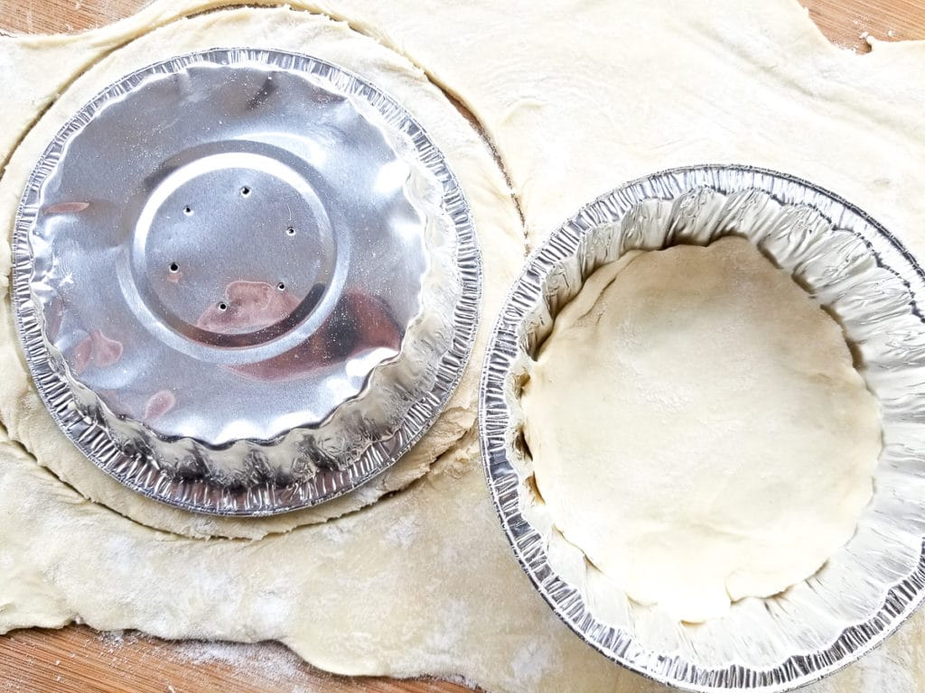 Mini tray faced down on top of dough faced down on pastry sheet. Dough cut in a circle slightly bigger than tray.