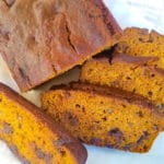 Pan de Calabaza (Pumpkin Bread) served on a white platter on top of white parchment paper.