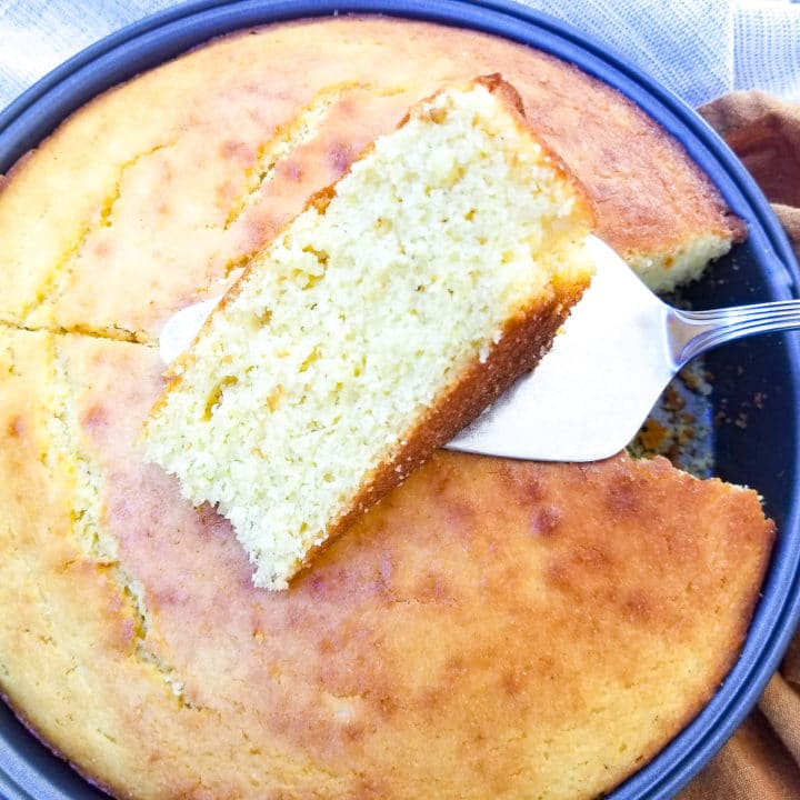 Pan de Maiz (Cornbread) fully cooked in a baking dish with a slice cut out and laying on top.