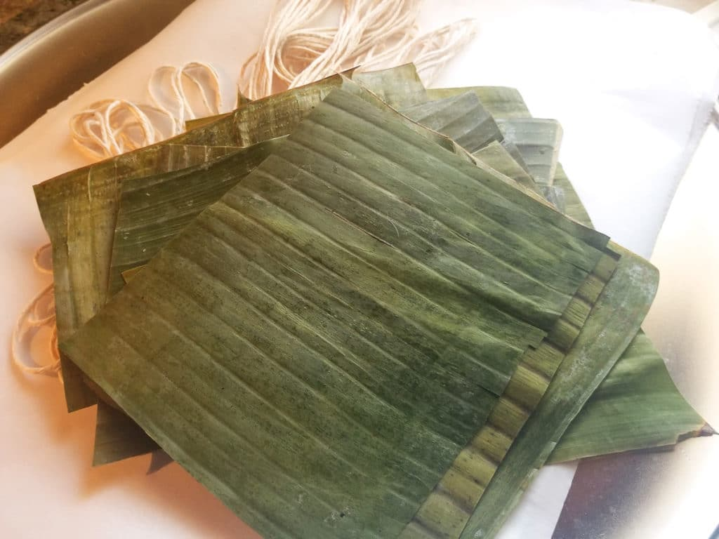 Plantain leaves, paper and twine ready for the pasteles.