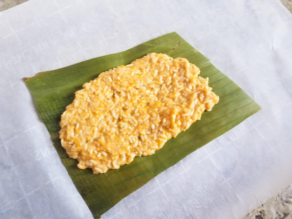 Rice added to plantain leaf to make pastel.