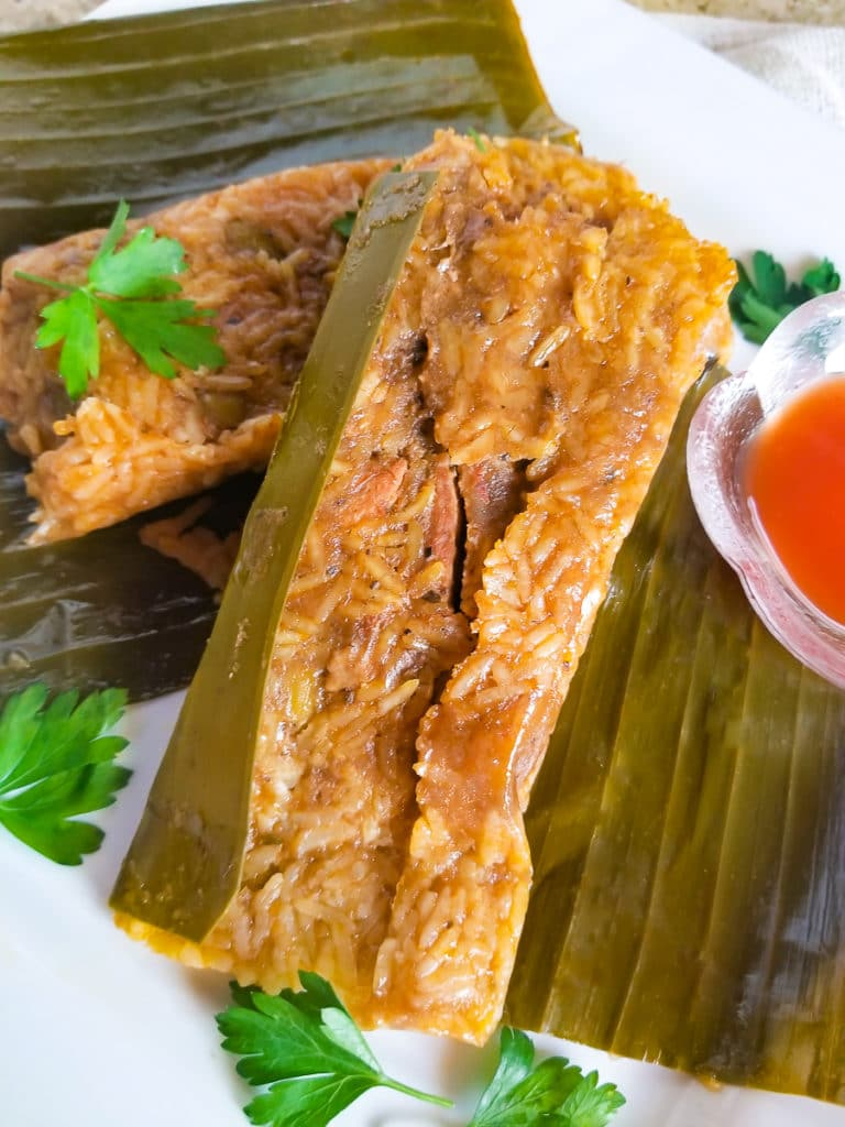 Pasteles de Arroz (Rice Pasteles) on a white plate with a side of hot sauce.
