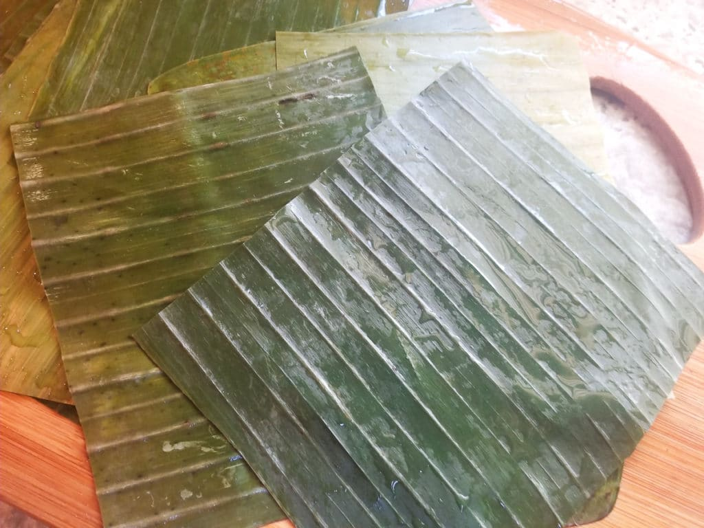 Plantain leaves washed, treated and laying on a wooden cutting board.