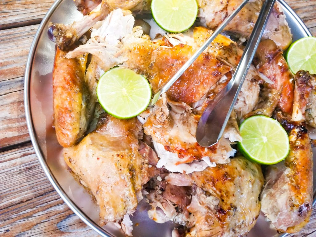 Turkey cut up and served on a silver platter with lime wedges around tray.