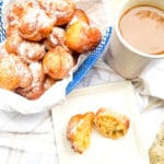 Plantain Puff Puffs served in a blue wire basket topped with confectioners sugar and coffee on the side.
