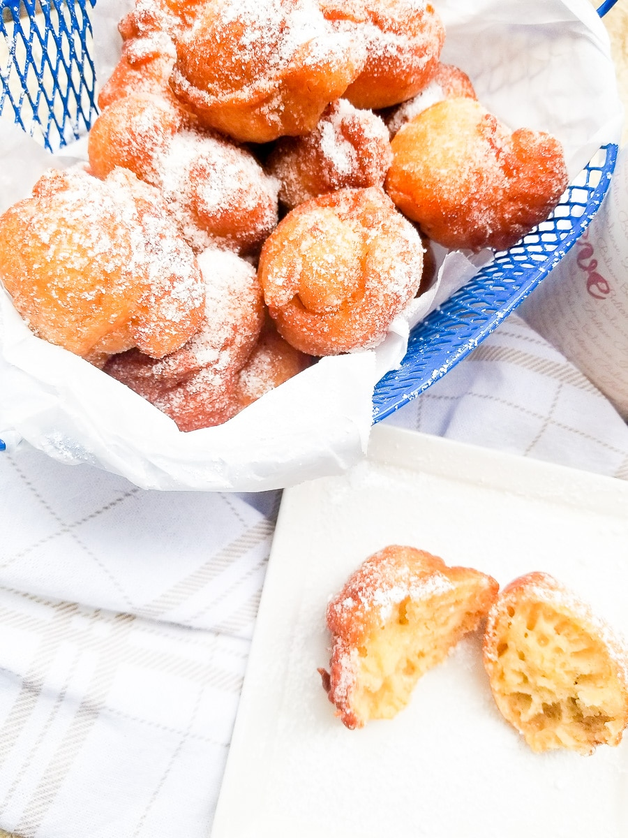 Plantain Puff Puff in a blue wire basket topped with confectioners sugar.