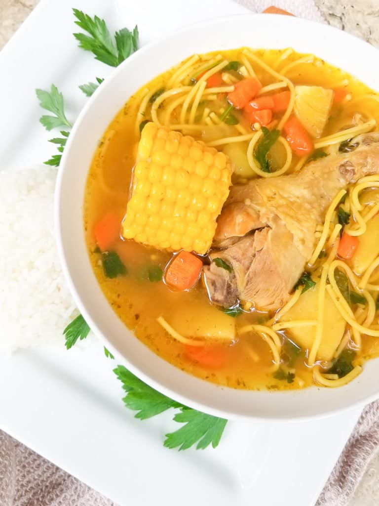Puerto Rican Chicken Soup (Sopa de Pollo Boricua) served in a large white bowl with a side of white rice.