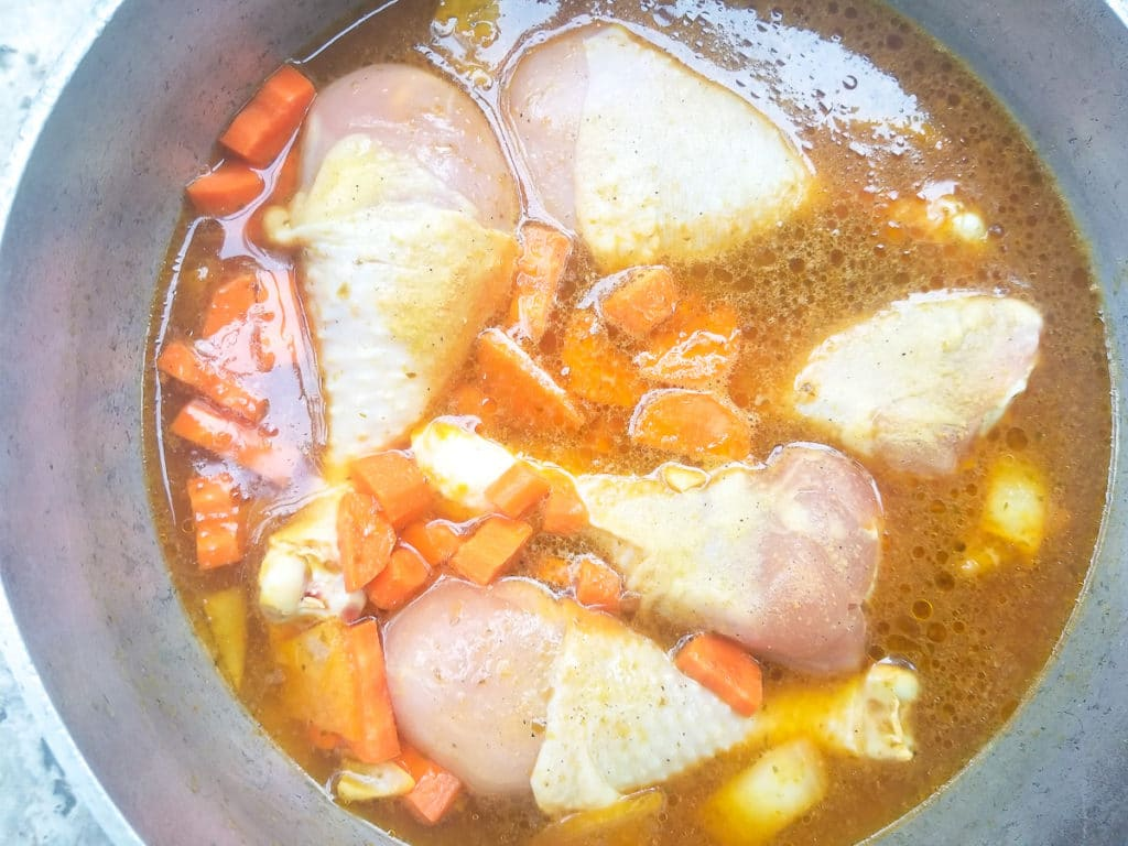 Chicken, carrots and broth cooking in a caldero.