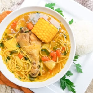Puerto Rican Chicken Soup (Sopa de Pollo) in a white bowl with white rice on the side.