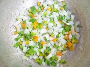 Onions and peppers cooking in a caldero for the criolla sauce.